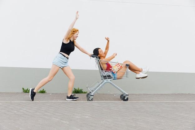 Mujer rodando novia con las manos levantadas en carro de compras