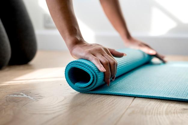 Mujer rodando tapete de yoga