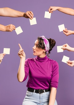 Mujer rodeada de manos y notas adhesivas escogiendo una nota vacía