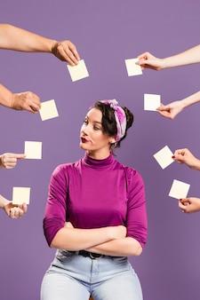 Mujer rodeada de manos y notas adhesivas sentado