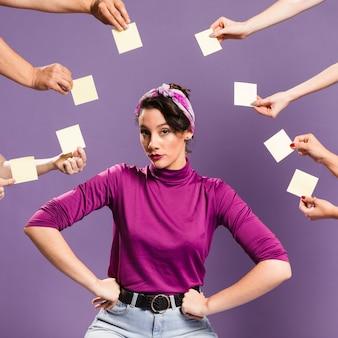 Mujer rodeada de manos y notas adhesivas