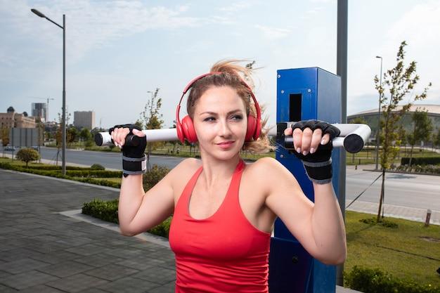 Mujer en rojo con auriculares rojos haciendo ejercicios de gimnasio en un espacio público.
