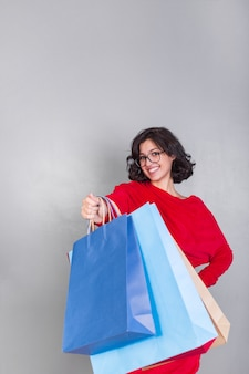 Mujer en rojo dando bolsas de compras