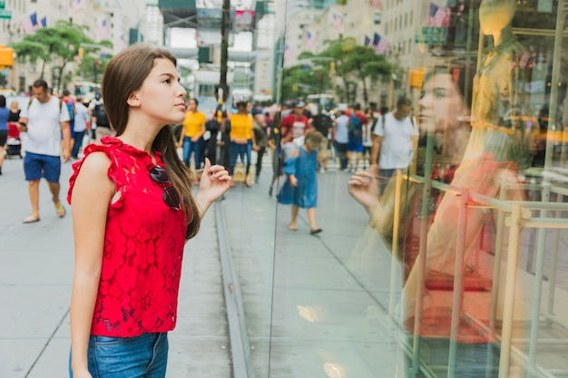Mujer en rojo mirando la ventana de la tienda