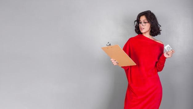 Mujer en rojo con portapapeles y tarjeta de crédito.
