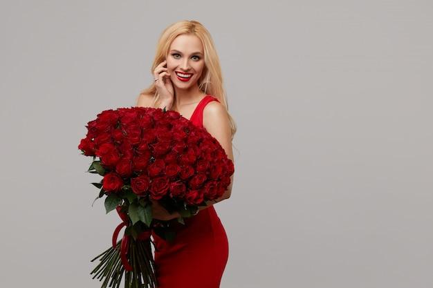 Mujer romántica belleza con ramo de flores rosas rojas. labios rojos. día de san valentín