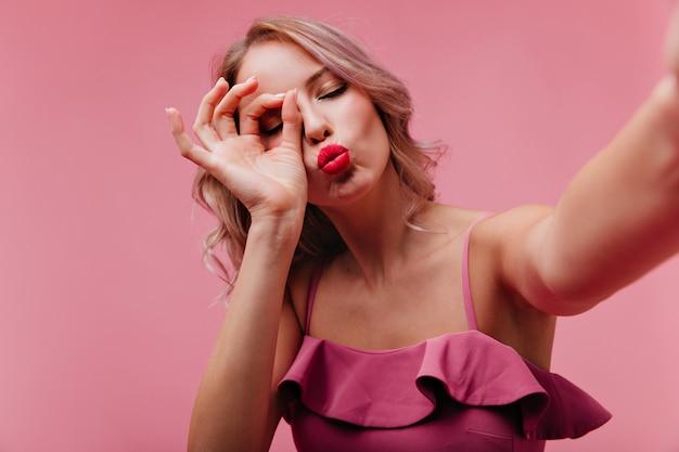 Mujer romántica con labios rojos posando con expresión de la cara de besos durante la sesión de fotos en interiores