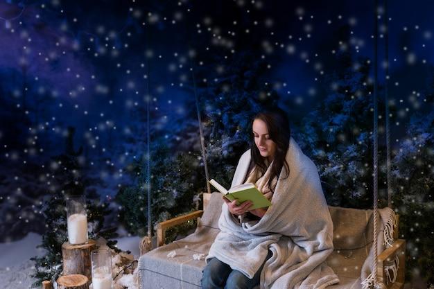Mujer romántica leyendo un libro mientras está sentada en un columpio y envuelta en una manta cálida por la noche en un parque cubierto de nieve con abetos, mientras nieva