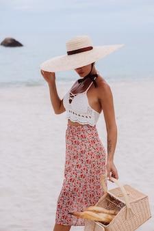 Mujer romántica en la playa en la parte superior de la falda de punto y sombrero de paja con canasta con pan eco vida