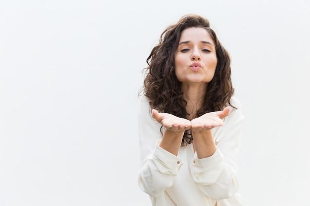 Mujer romántica positiva enviando beso de aire
