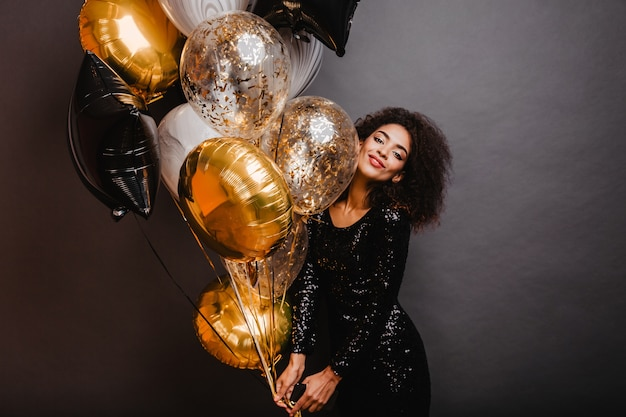 Mujer romántica con ramo de globos de fiesta