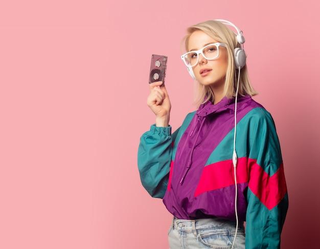 Mujer en ropa de los 90 con auriculares y cassette de audio