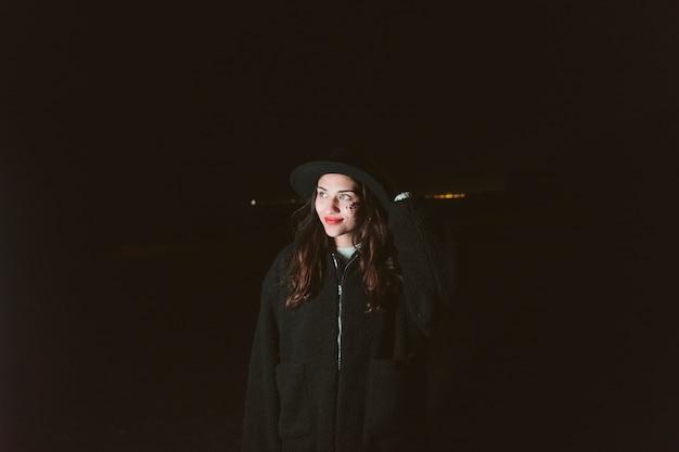 Mujer en ropa de abrigo de pie en la calle oscura