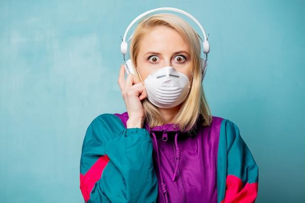 Mujer en ropa de los años 90 y mascarilla con auriculares