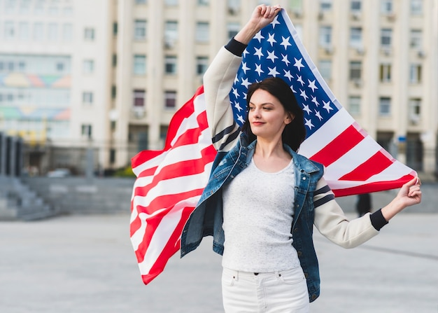 Mujer en ropa blanca con bandera americana en la calle