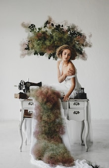La mujer en la ropa blanca se sienta en una habitación con flores y una máquina de coser