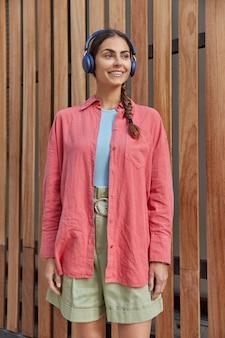 Mujer en ropa casual de buen humor escucha música en auriculares mientras va de compras se encuentra al lado de madera, por lo tanto, disfruta del tiempo libre se reúne con un amigo en los fines de semana soleados de primavera