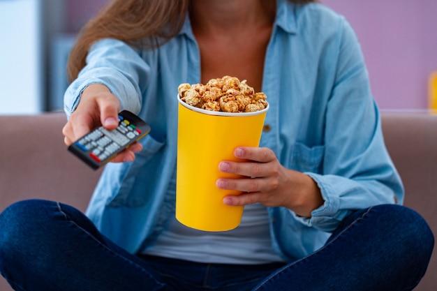 Mujer en ropa casual descansando y comiendo palomitas crujientes de caramelo mientras mira televisión