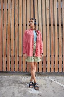 Mujer en ropa casual posa cerca de madera, por lo tanto, al aire libre durante el día mira hacia otro lado. estudiante escucha música de radio de podcast a través de una aplicación musical.