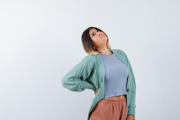 Mujer en ropa casual sosteniendo la mano en la cintura y mirando esperanzada, vista frontal.