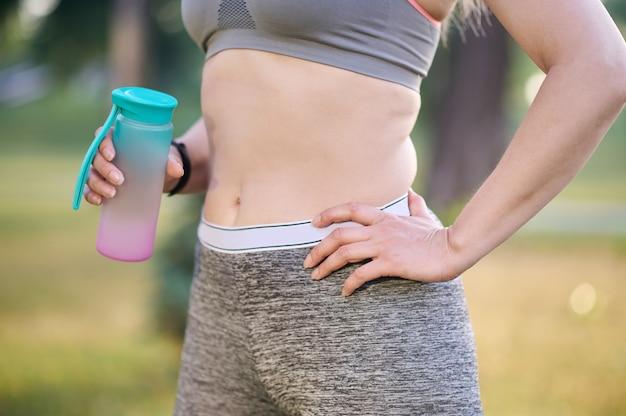 Una mujer en ropa deportiva con una botella en las manos.