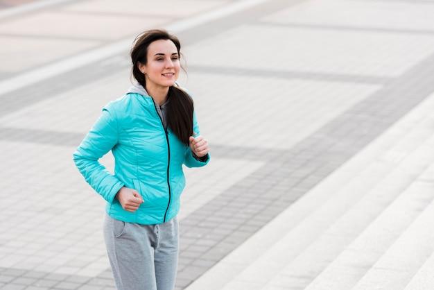 Mujer en ropa deportiva corriendo en las escaleras