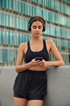 Mujer en ropa deportiva descarga canciones a la lista de reproducción para hacer ejercicio lee noticias sobre la última competencia navega por el sitio web comprueba la notificación de la aplicación deportiva posa contra el edificio de cristal