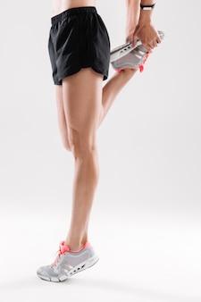 Mujer en ropa deportiva estirando su pierna