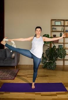 Mujer en ropa deportiva hace un estiramiento con un cinturón sobre una estera en la habitación