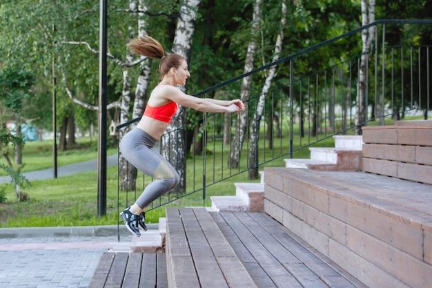 Mujer en ropa deportiva hacer sentadillas en los escalones de madera de las escaleras en un parque de la ciudad en verano.