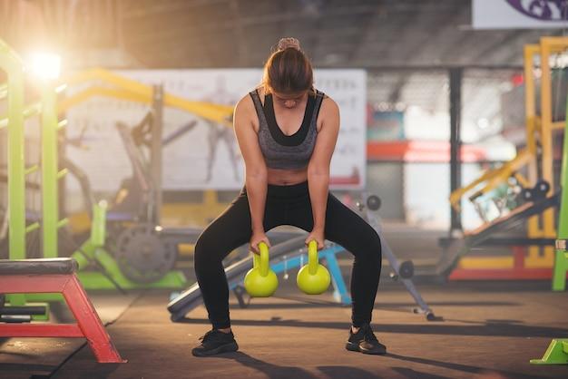 Mujer en ropa deportiva haciendo ejercicios de crossfit con campana caldera. concepto saludable