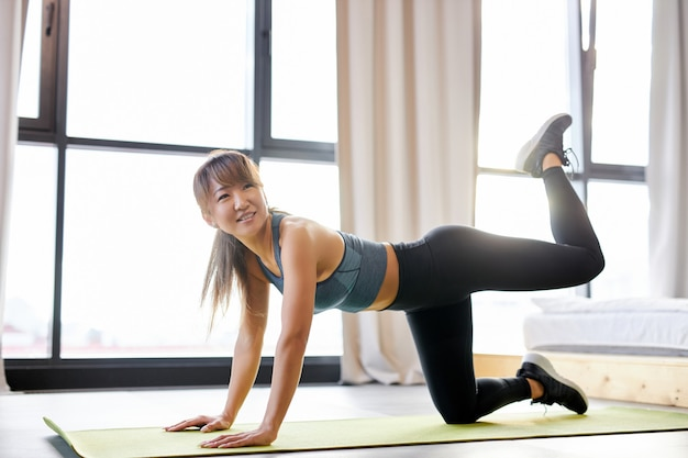 Mujer en ropa deportiva haciendo ejercicios de estiramiento de fitness en casa en una habitación luminosa. deporte, estilo de vida saludable y concepto de recreación.