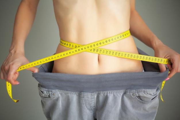 Mujer en ropa deportiva midiendo su cintura, concepto de dieta
