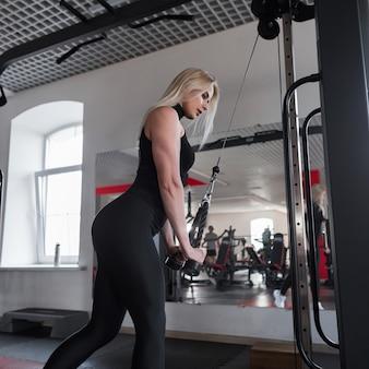 Mujer en ropa deportiva negra está entrenando en el gimnasio