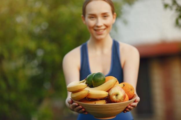 Mujer en ropa deportiva tiene una fruta