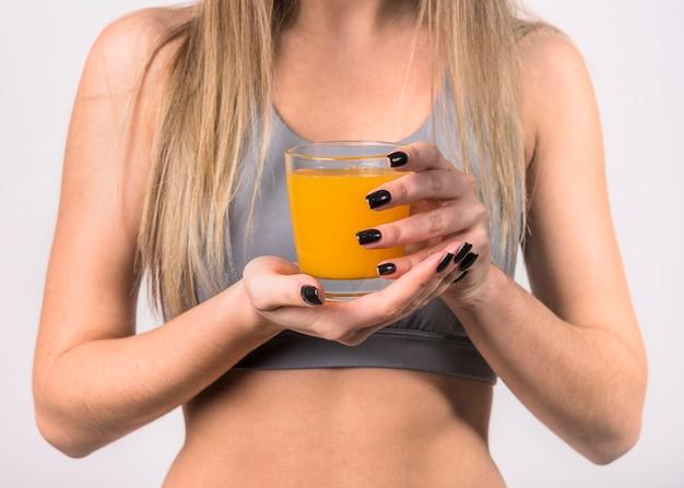 Mujer en ropa deportiva con vaso de jugo