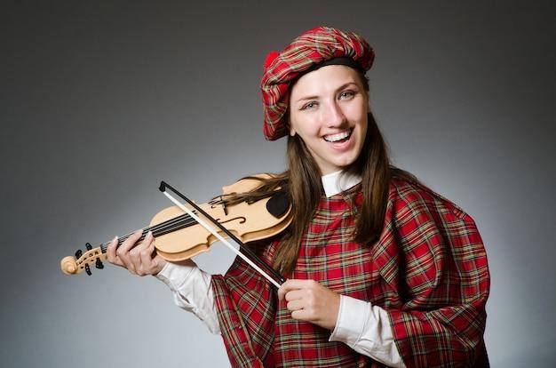 Mujer en ropa escocesa en musical.