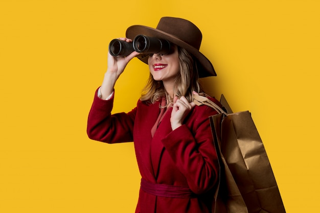 Mujer en ropa de estilo años 40 con binoculares y bolsos