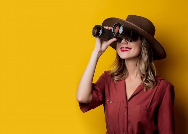 Mujer en ropa de estilo años 40 con binoculares