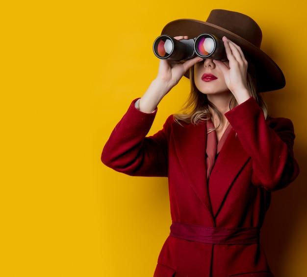 Mujer en ropa de estilo años 40 y binoculares