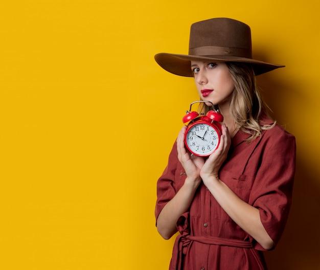 Mujer en ropa de estilo años 40 con despertador