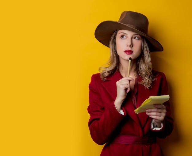 Mujer en ropa de estilo años 40 con libreta y bolígrafo
