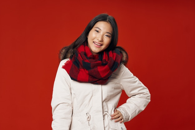 Mujer en ropa de invierno bufanda a cuadros sonrisa apariencia asiática frescura de estilo de vida de invierno rojo