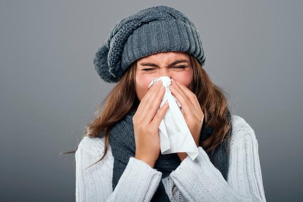 Mujer en ropa de invierno estornudos