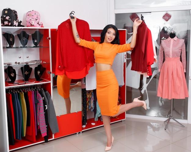 Mujer con ropa en las manos y una pierna levantada