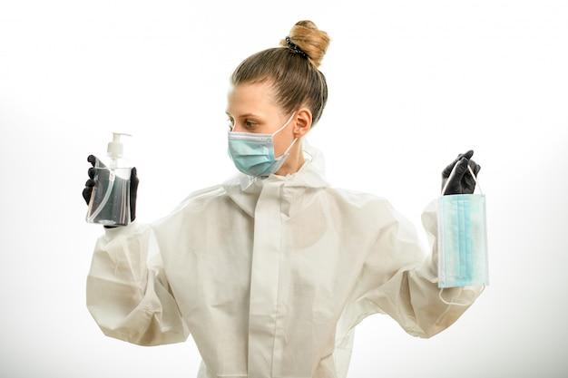 Mujer en ropa protectora tiene máscara y desinfectante en sus manos y mira a su lado derecho