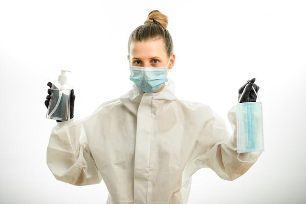 Mujer en ropa protectora tiene máscara y desinfectante en sus manos.