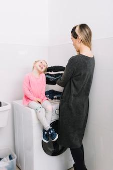 Mujer con ropa sucia mirando a su hija linda sentada en la lavadora