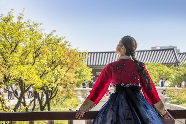 Mujer en ropa tradicional coreana mirando al cielo