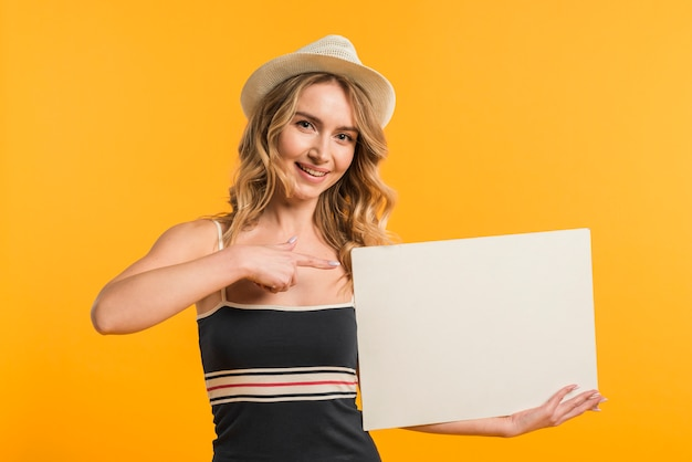 Mujer en ropa de verano apuntando al papel en blanco